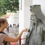Mona berührt Stein-Wächter im Tempel in Bangkok