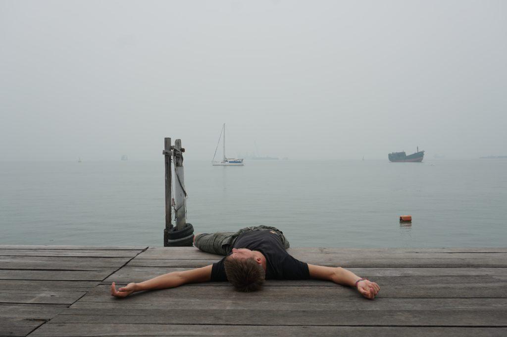 Marcel auf einem nebligen Steg liegend mit Umrissen von Booten im Hintergrund.