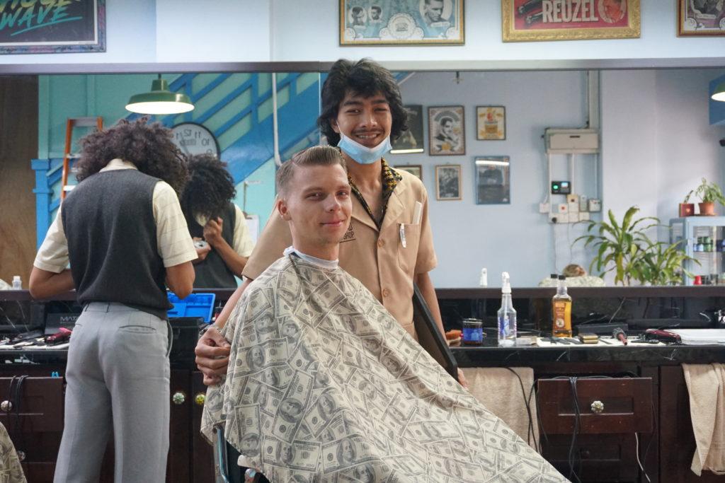 Marcel mit Friseurkittel an und Pomade in den Haaren in einem Friseursalon in Georgetown