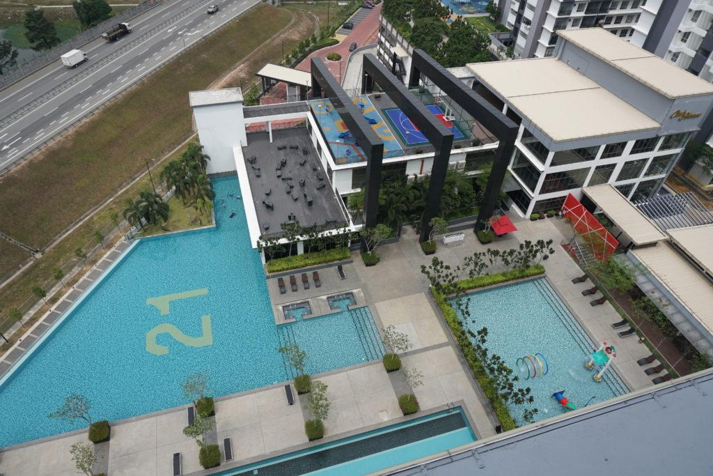Ansicht auf großen Pool und Fitnessstudio des BSP21-Wohnkomplexes aus der Vogelperspektive.