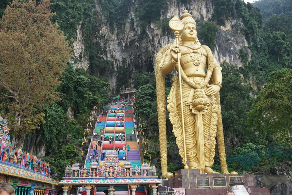 Goldene Gottheiten-Statuen am Eingang der Batu Cave und bunte Treppe
