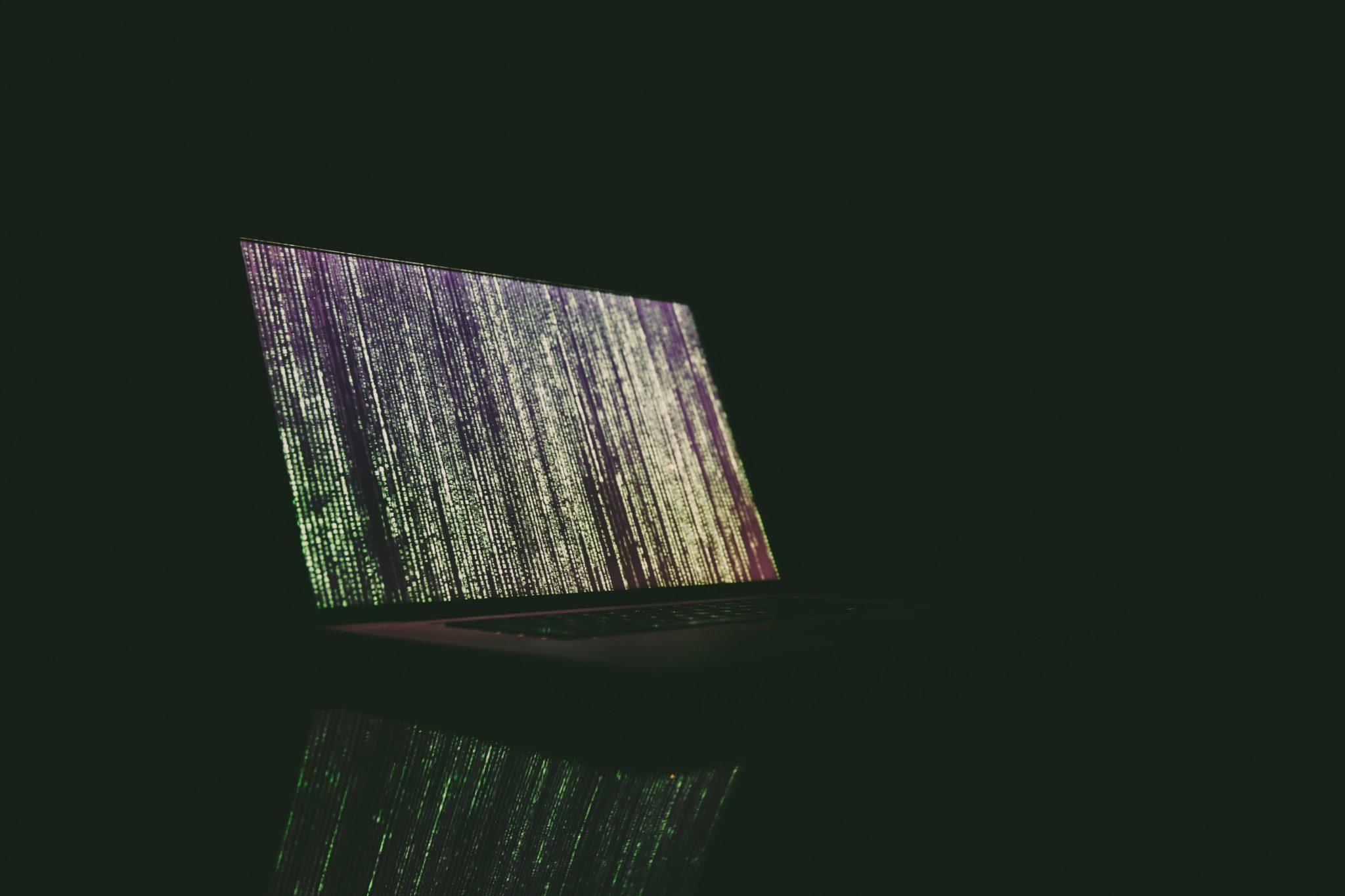 Laptop mit vielen vertikalen grünen Zeichenreihen auf dem Bildschirm in dunklem Raum.