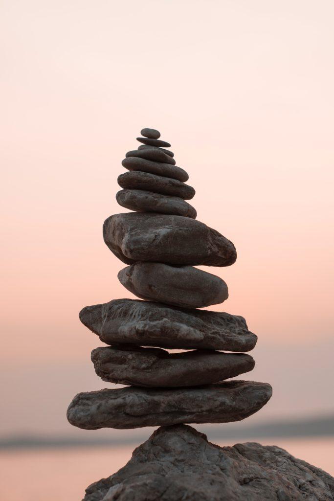 Turm aus Steinen vor lilanem Hintergrund
