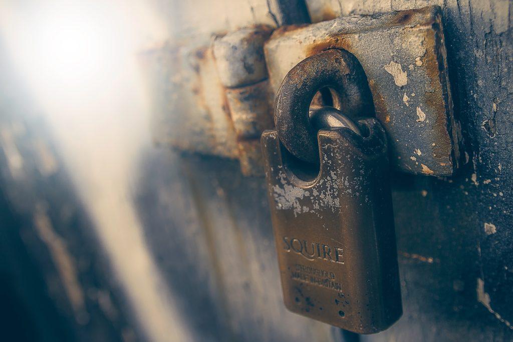 Rostiges Vorhängeschloss vor Türriegel als Symbol für sichere Passwörter. Photo by James Sutton on Unsplash.