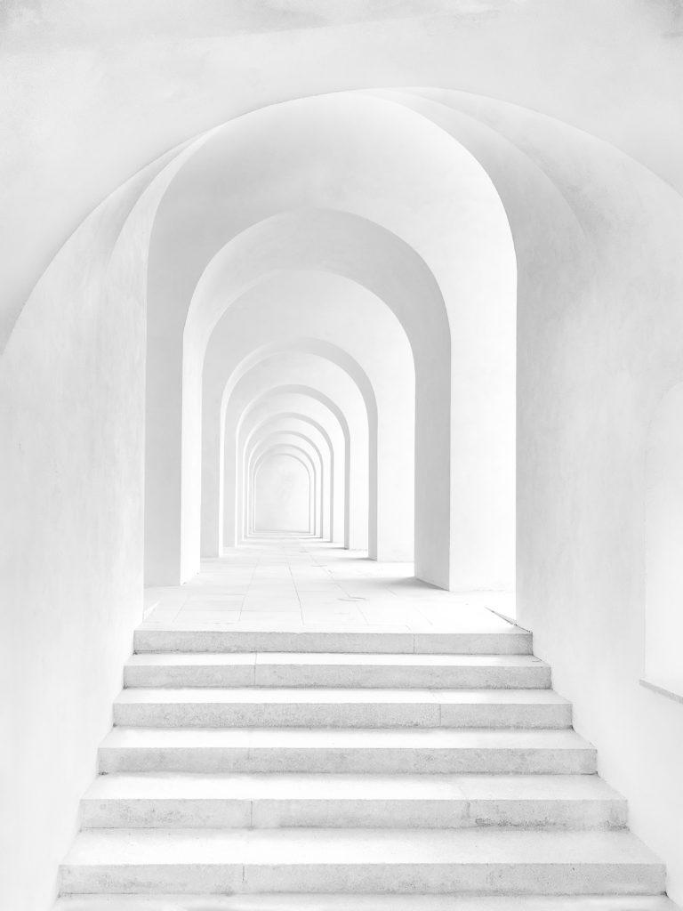 Weiße Treppe mit einer Reihe weißer Türöffnungen hintereinander.