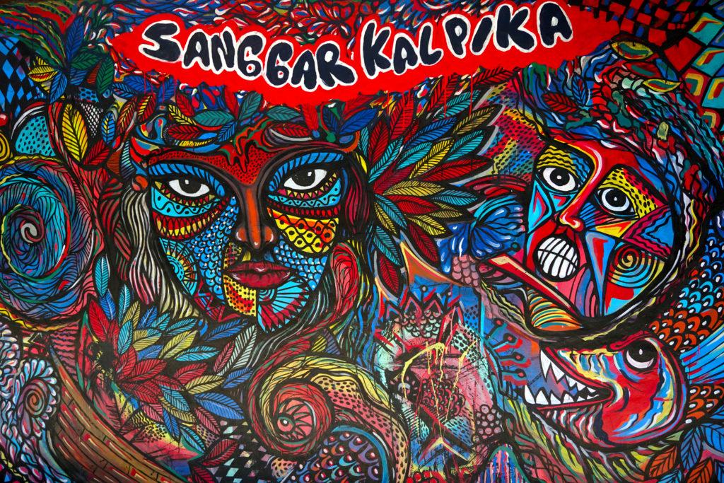 """Buntes Graffitti mit zwei Gesichtern und der Aufschrift """"Sanggar Kalpika"""""""