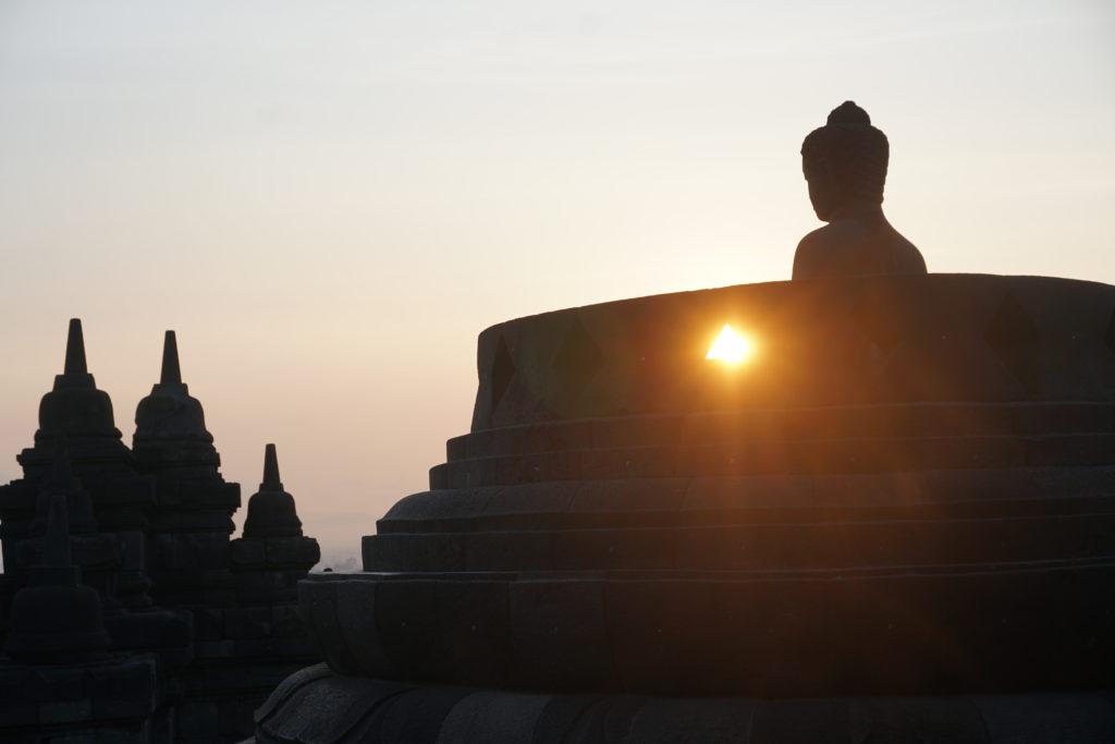 Morgensonne, wie sie durch den Sockel einer Buddha-Statue in Borobudur scheint.