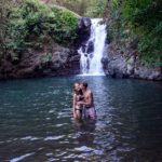 Marcel küsst Mona im Wasser vor einem Wasserfall.