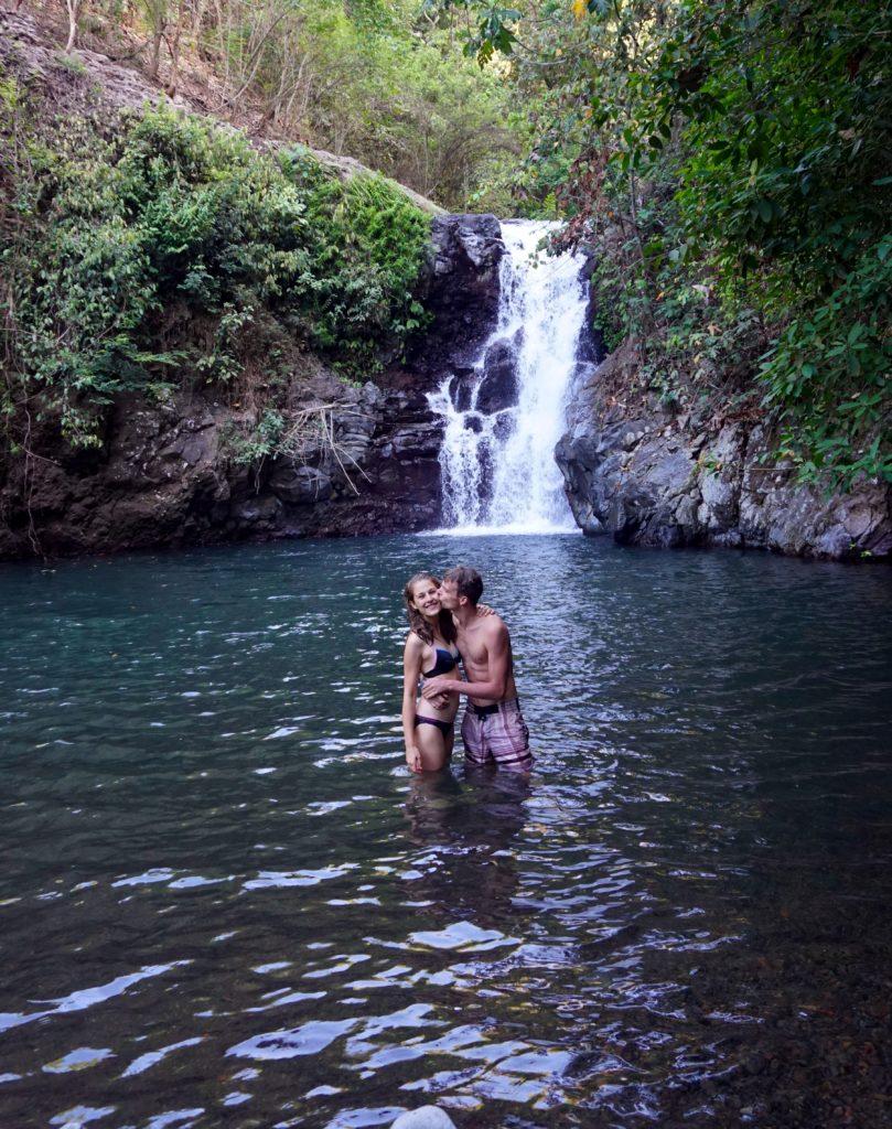 Marcel küsst Mona neben dem Wasserfall nach ihrem Sprung aus 10 Metern Höhe.