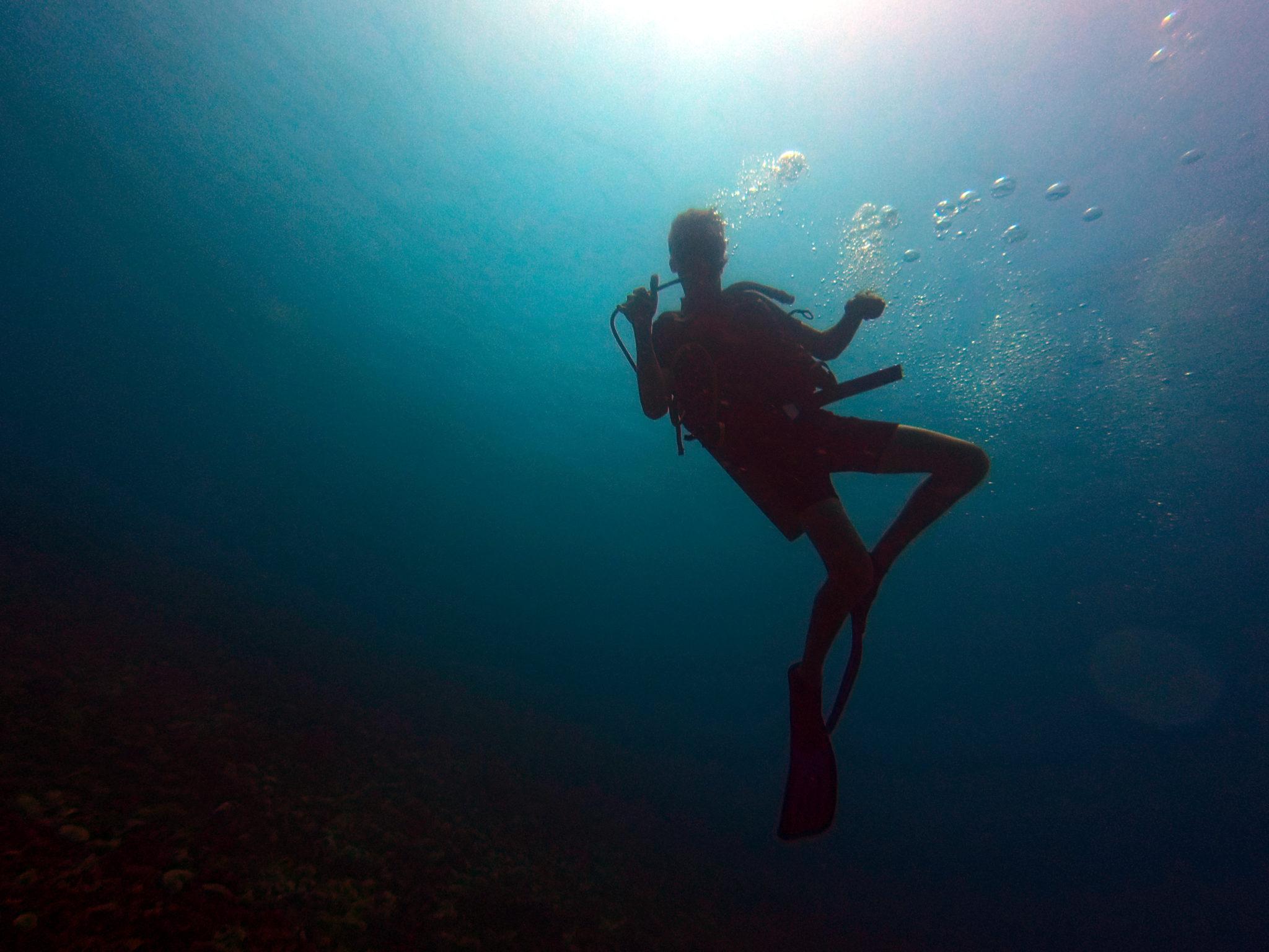 Umrisse von Marcel mit Tauchausrüstung unter Wasser.
