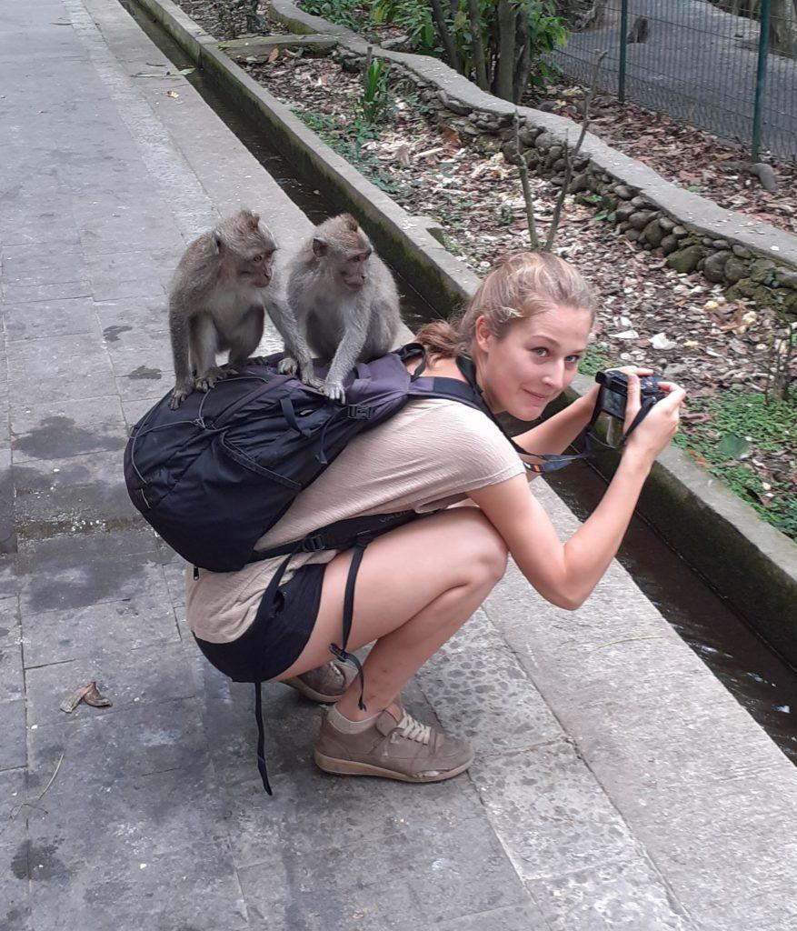 Mona im Hocken mit zwei Affen auf dem Rücken.