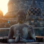 Buddha-Statue in Borobudur, die sanft von der Morgensonne angestrahlt wird.