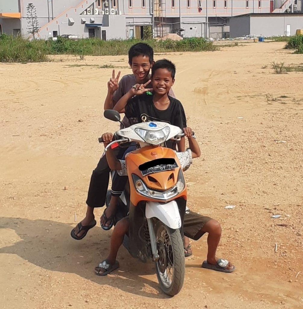 Foto von drei kleinen Jungs auf einem Roller.