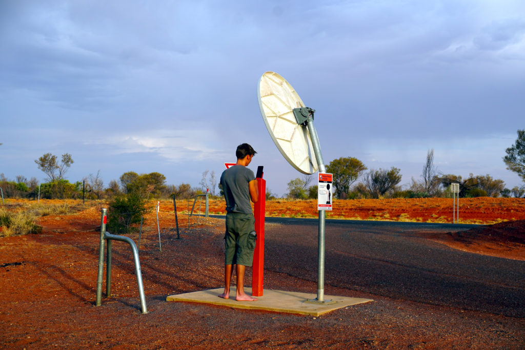 Marcel beim Telefonieren unter einer Satellitenschüssel am Outback-Parkplatz