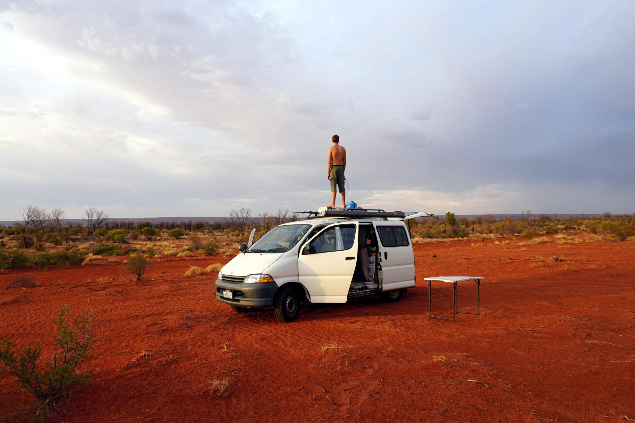 Marcel auf Campervan stehend mitten im australischen Outback