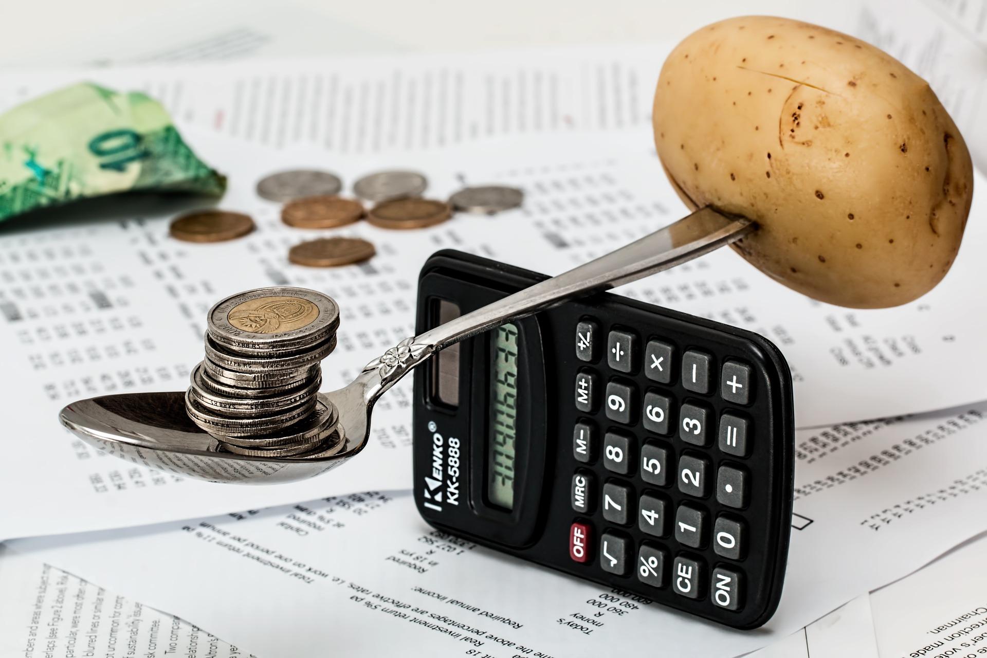 Löffel-Waage mit Münzen auf der einen und Kartoffeln auf der anderen Seite. Symbol für das bedingungslose Grundeinkommen.