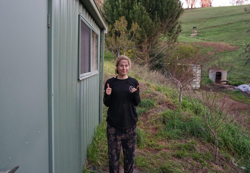 Mona in dreckigen Arbeitsklamotten vor ihrer Hütte