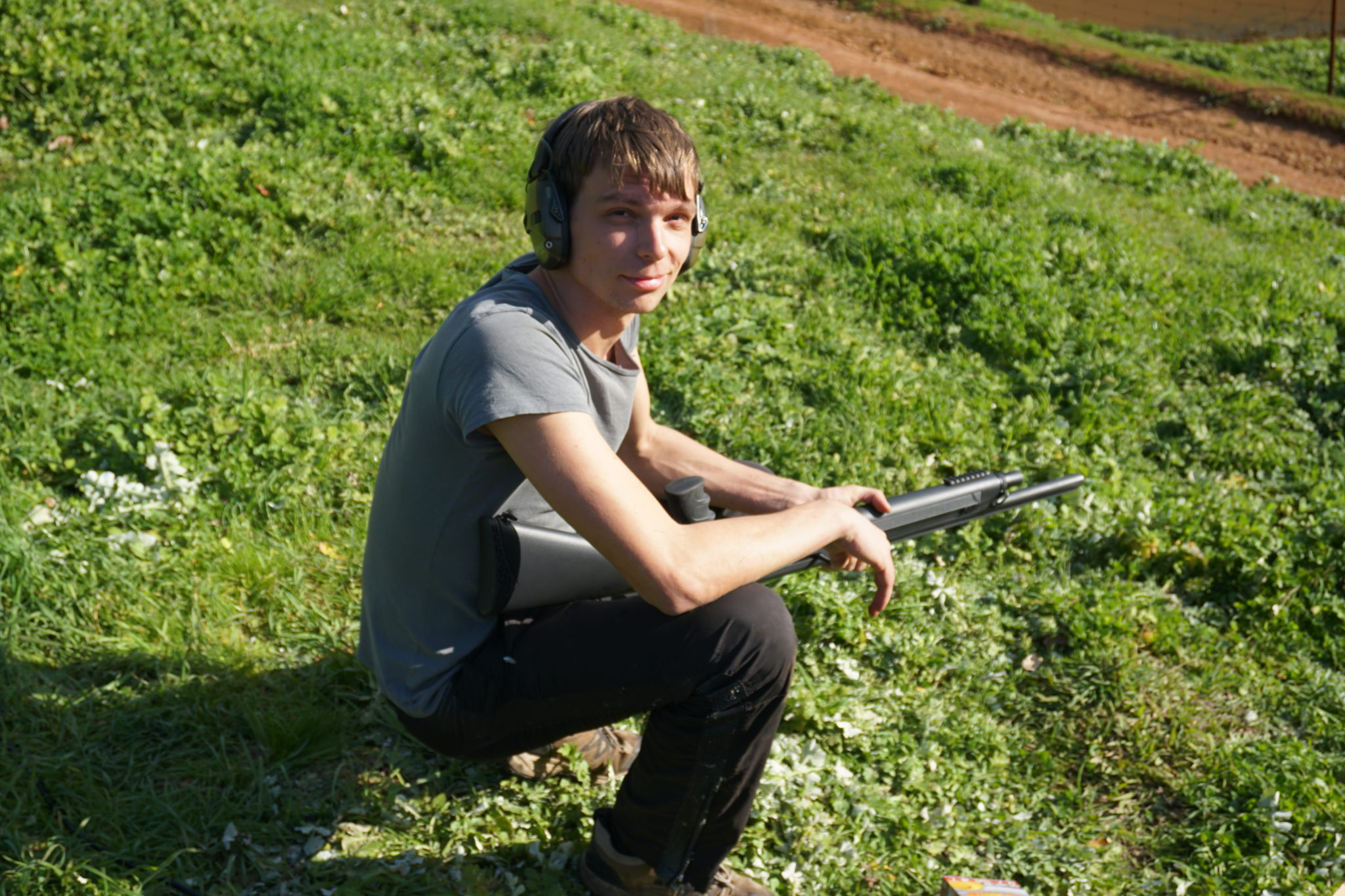 Marcel im Gras hockend mit Shotgun
