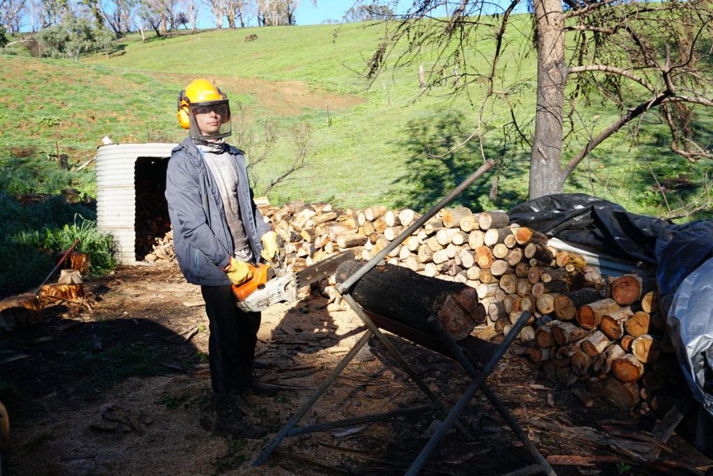 Marcel mit Kettensäge vor gehacktem Holz