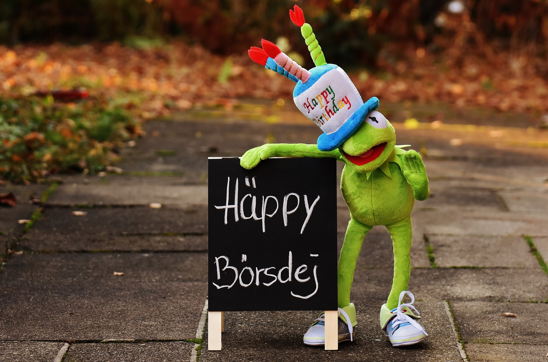 Frosch hält Tafel mit Aufschrift: Häppy Börsdej
